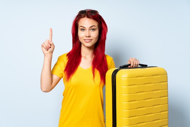 Ragazza del viaggiatore che giudica una valigia isolata sulla parete blu che indica su una grande idea