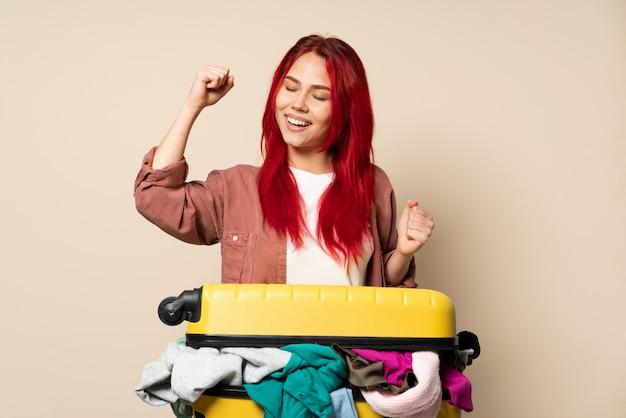 Ragazza del viaggiatore con una valigia piena di vestiti isolati su fondo beige che celebra una vittoria