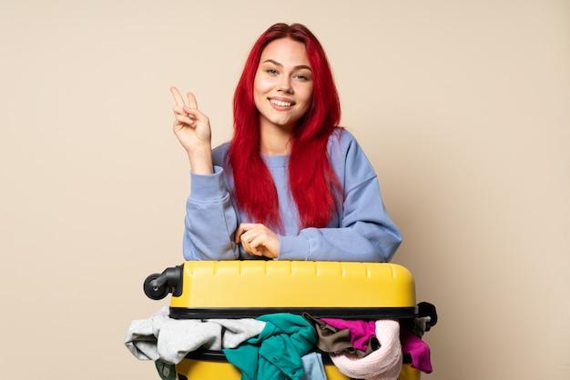 Ragazza del viaggiatore con una valigia piena di vestiti isolati su fondo beige che sorride e che mostra il segno di vittoria