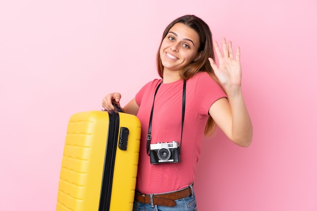 Ragazza del viaggiatore dell'adolescente che tiene una valigia sopra il saluto rosa isolato con la mano con l'espressione felice
