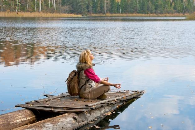 Ragazza del viaggiatore sul vecchio molo di legno