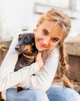Ragazza dell'adolescente che abbraccia il suo cane del bassotto tedesco all'aperto