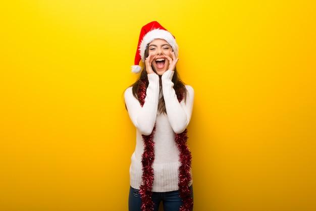 Ragazza dell'adolescente che celebra le feste di natale che gridano con la bocca spalancata