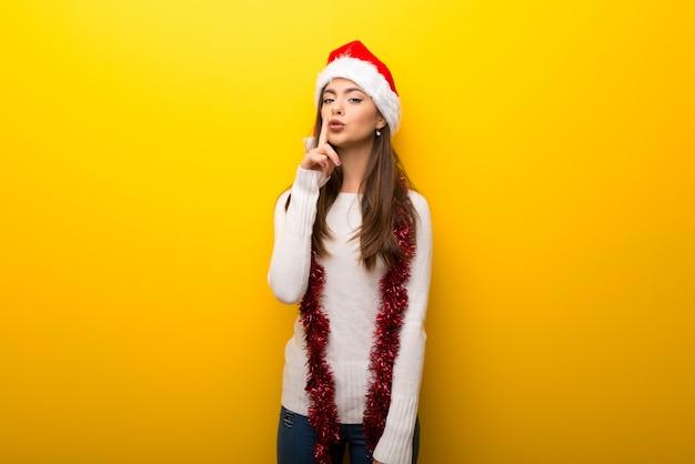 Ragazza dell'adolescente che celebra le feste di natale che mostrano un segno della bocca di chiusura e del gesto di silenzio