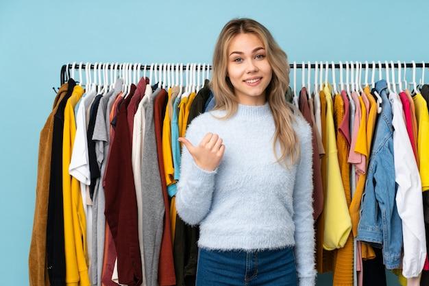 Ragazza dell'adolescente che compra alcuni vestiti sulla parete blu che indica il lato