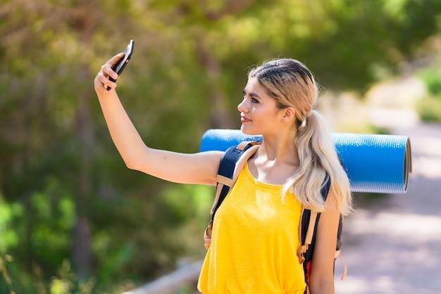 Ragazza dell'adolescente che fa un'escursione ad all'aperto che fa un selfie