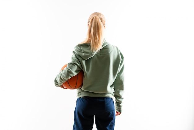 Ragazza dell'adolescente che gioca pallacanestro sopra bianco isolato