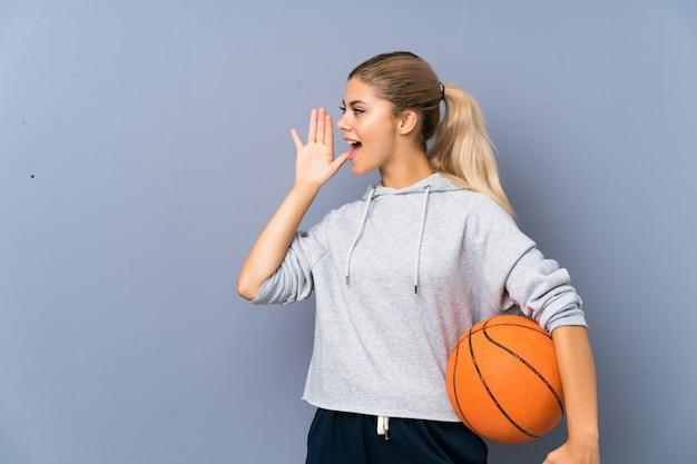 Ragazza dell'adolescente che gioca pallacanestro sopra la parete grigia che grida con la bocca spalancata