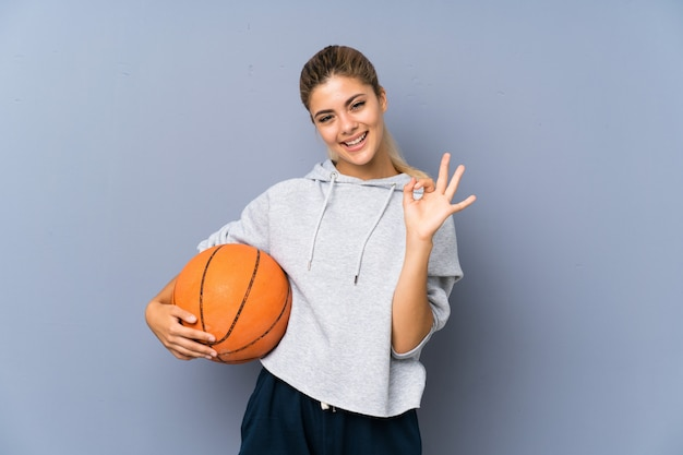 Ragazza dell'adolescente che gioca pallacanestro sopra la parete grigia che mostra segno giusto con le dita