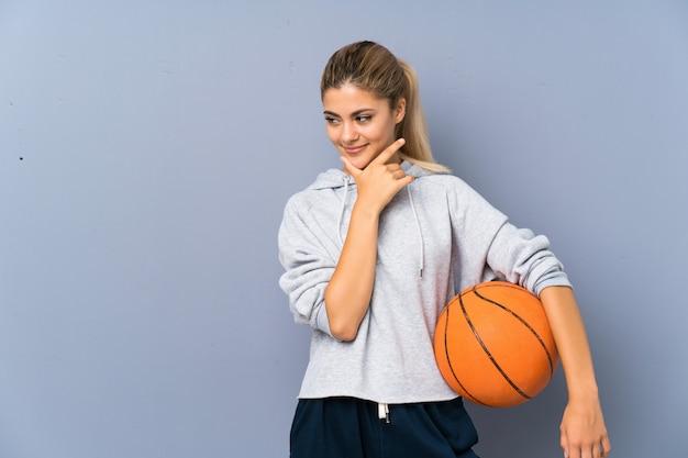 Ragazza dell'adolescente che gioca pallacanestro sopra la parete grigia che pensa un'idea