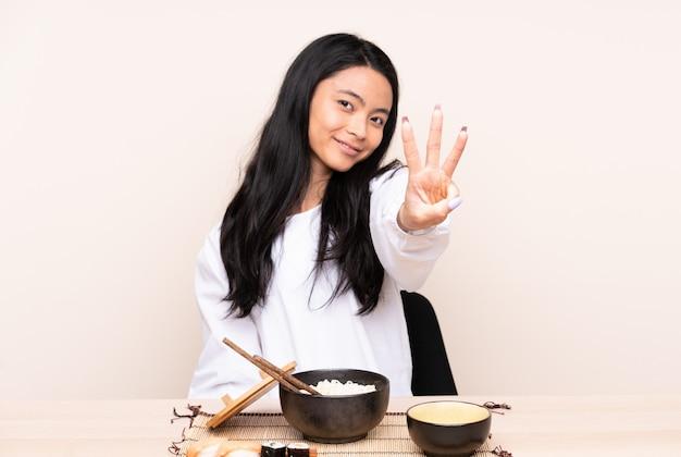 Ragazza dell'adolescente che mangia alimento asiatico isolato su felice beige e che conta tre con le dita