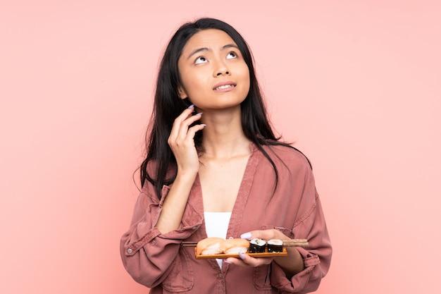 Ragazza dell'adolescente che mangia i sushi isolati sul rosa che pensa un'idea