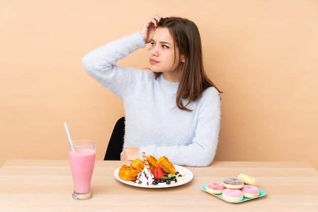 Ragazza dell'adolescente che mangia i waffles isolati sulla parete beige che ha dubbi mentre graffiando la testa