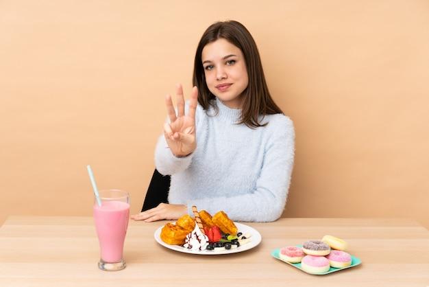 Ragazza dell'adolescente che mangia i waffles su beige felice e che conta tre con le dita