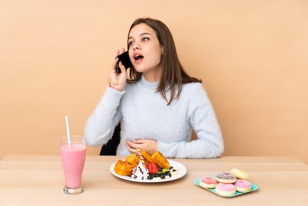 Ragazza dell'adolescente che mangia i waffles sul beige che mantiene una conversazione con il telefono cellulare