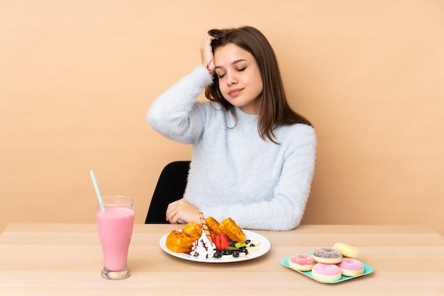 Ragazza dell'adolescente che mangia le cialde sulla parete beige con un'espressione di frustrazione e di non comprensione
