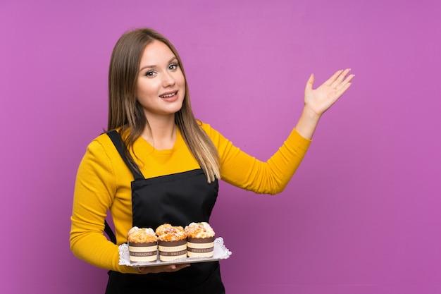 Ragazza dell'adolescente che tiene i lotti di mini torte differenti sopra fondo porpora isolato che estende le mani al lato per l'invito a venire