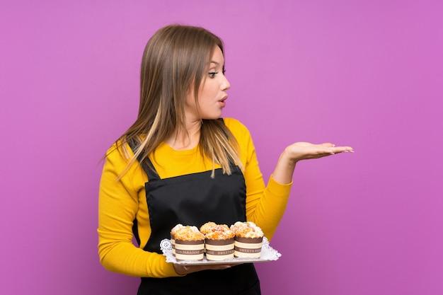 Ragazza dell'adolescente che tiene i lotti di mini torte differenti sopra fondo porpora isolato che giudica copyspace immaginario sulla palma