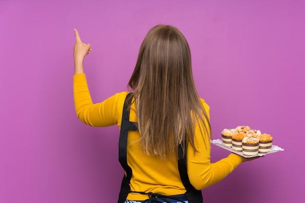 Ragazza dell'adolescente che tiene i lotti di mini torte differenti sopra la parete viola isolata che indica indietro con il dito indice