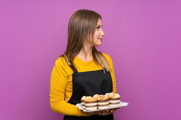 Ragazza dell'adolescente che tiene i lotti di mini torte differenti sopra la parete viola isolata che osserva al lato