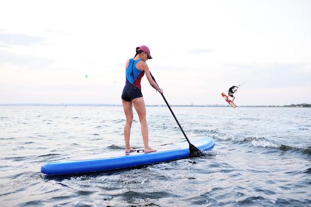 Ragazza dell'adolescente con il bordo del sup sul mare. attività di paddle surf
