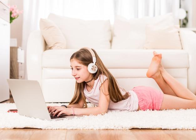 Ragazza dell'adolescente con il computer portatile sul pavimento