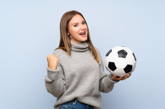 Ragazza dell'adolescente con il maglione sopra fondo blu isolato che tiene un pallone da calcio