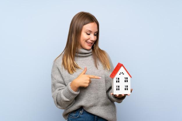Ragazza dell'adolescente con il maglione sopra fondo blu isolato che tiene una piccola casa