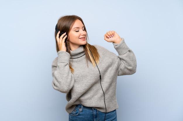 Ragazza dell'adolescente con il maglione sopra la parete blu isolata che ascolta la musica con le cuffie