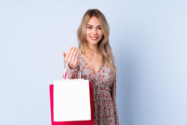 Ragazza dell'adolescente con il sacchetto della spesa sulla parete blu che invita a venire con la mano.