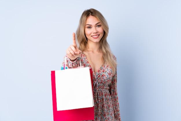 Ragazza dell'adolescente con il sacchetto della spesa sulla parete blu che mostra e che solleva un dito