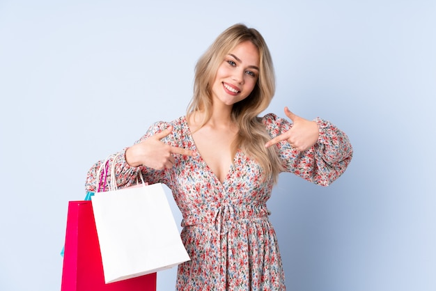 Ragazza dell'adolescente con il sacchetto della spesa sulla parete blu fiera e soddisfatta di sé