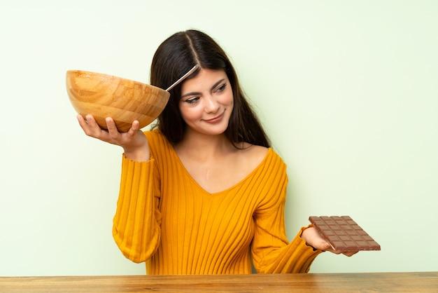 Ragazza dell'adolescente con insalata e cioccolato che hanno dubbi