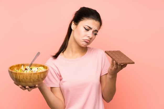 Ragazza dell'adolescente con insalata e cioccolato e avere dubbi