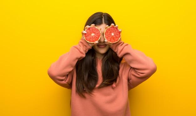 Ragazza dell'adolescente con la maglietta felpata rosa su fondo giallo che indossa le fette arancio come vetri