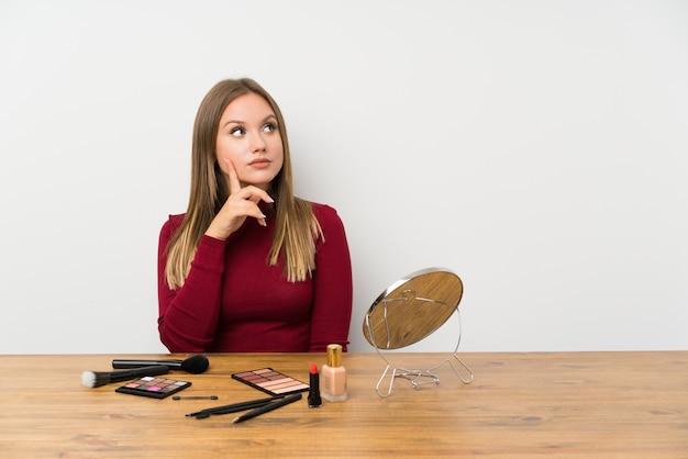 Ragazza dell'adolescente con la tavolozza e i cosmetici di trucco in una tavola che pensa un'idea