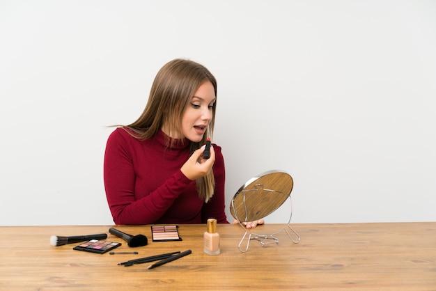 Ragazza dell'adolescente con la tavolozza e i cosmetici di trucco in una tavola
