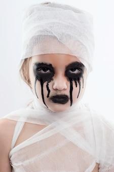 Ragazza dell'adolescente con le fasciature della mummia su halloween su bianco isolato