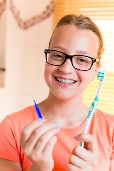 Ragazza dell'adolescente con le parentesi graffe dentali che puliscono i suoi denti