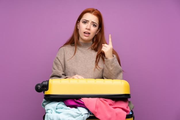 Ragazza dell'adolescente del viaggiatore con una valigia piena di vestiti che indica con il dito indice una grande idea