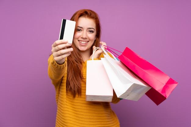 Ragazza dell'adolescente della testarossa sopra i sacchetti della spesa porpora isolati della tenuta della parete e una carta di credito