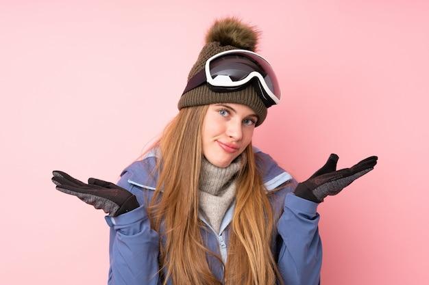 Ragazza dell'adolescente dello sciatore con i vetri di snowboard sopra il rosa isolato che ha dubbi con l'espressione confusa del fronte