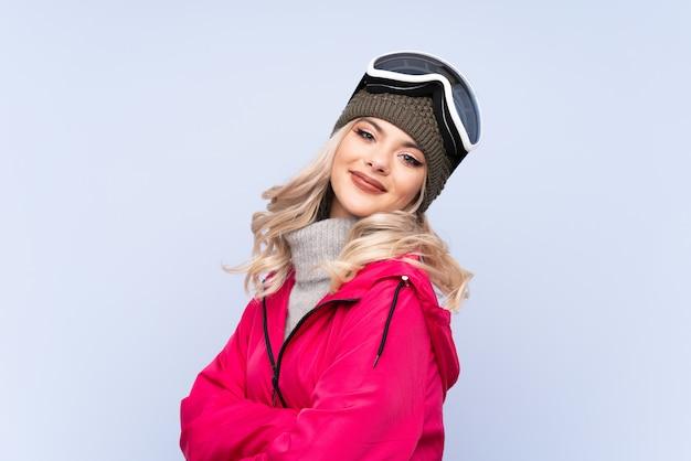 Ragazza dell'adolescente dello sciatore con i vetri di snowboard sopra la risata blu isolata