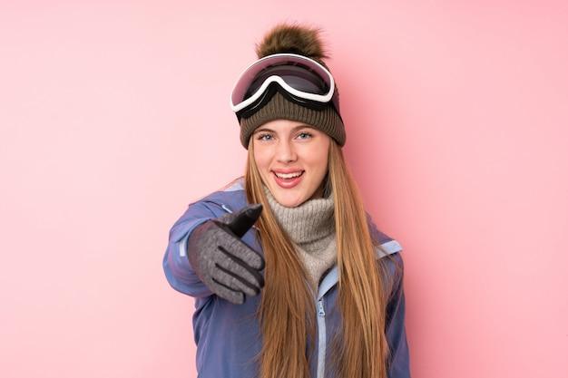 Ragazza dell'adolescente dello sciatore con i vetri di snowboard sopra la stretta di mano rosa isolata dopo il buon affare
