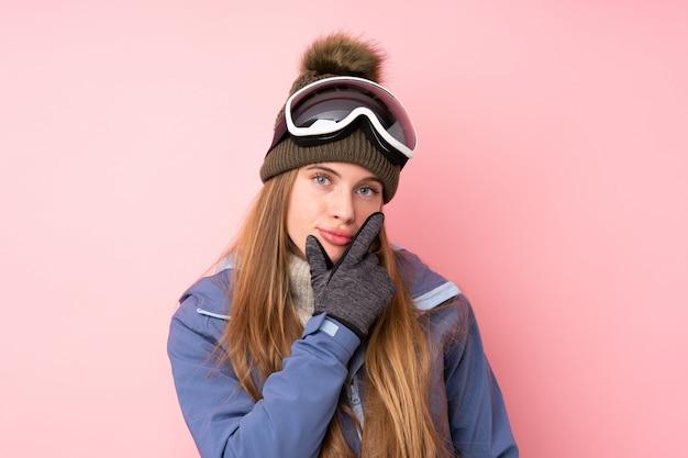 Ragazza dell'adolescente dello sciatore con il fondo di vetro di snowboard che pensa un'idea