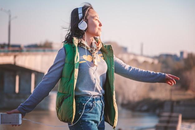 Ragazza dell'adolescente di 16 anni che ascolta la musica sulle cuffie in telefono all'aperto al tramonto