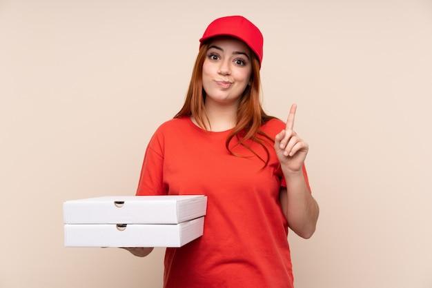 Ragazza dell'adolescente di consegna della pizza che tiene una pizza che indica con il dito indice una grande idea