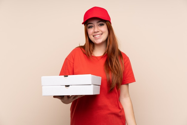Ragazza dell'adolescente di consegna della pizza che tiene una pizza sopra l'applauso isolato della parete