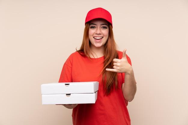 Ragazza dell'adolescente di consegna della pizza che tiene una pizza sopra la parete isolata che fa gesto del telefono