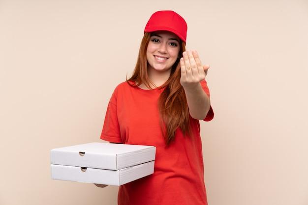 Ragazza dell'adolescente di consegna della pizza che tiene una pizza sopra la parete isolata che invita a venire